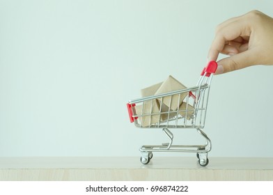 Woman hand forefinger pushing small shopping cart with Internet online shopping concept