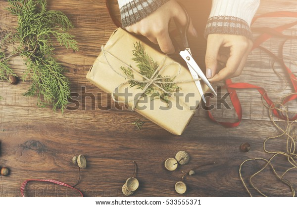 woman hand gift on wooden background, Rustic style with fir-tree and craft paper