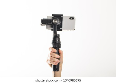 woman hand and gimbal with phone on white background
