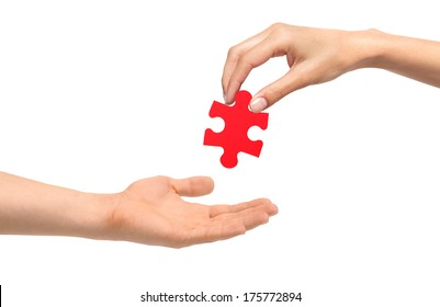 Woman hand give red puzzle to man hand isolated on white background