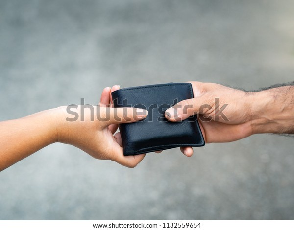 The woman hand give the wallet to the man.  Money & Financial concept.