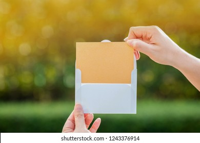 Woman hand giving a gift voucher or a business cards to customer or partners on bokeh background in the public park, For shopping or Introduce yourself concept.