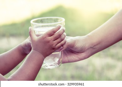 Woman hand giving glass of fresh water to little child girl in the park,vintage color filter