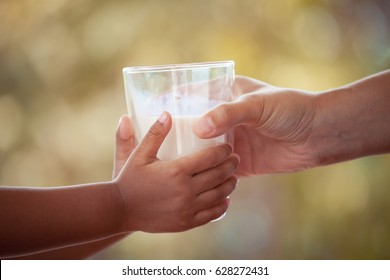 Woman hand giving glass of milk to child in vintage color tone