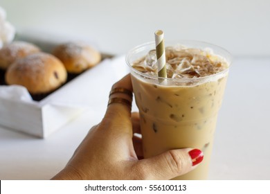 Woman hand with glass of cold coffee and sweet buns, hand in frame.
