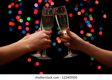 woman hand with glasses of champagne, on garland background