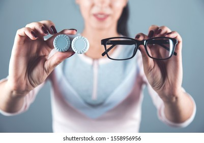 woman hand glasses with lenses on gray background