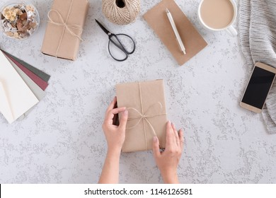 Woman hand with Handmade wrapped gift boxes on white and gray textured table background, top view and flat lay. Packing of gifts, writing envelopes for the autumn or winter holiday