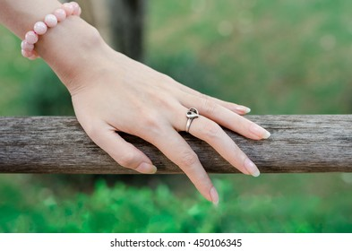 Woman hand with heart shaped ring of silver on wooden bridge.