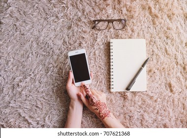 Woman hand with henna art using smartphone and blank notebook with eyeglasses on carpet, copy space