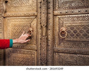 Woman hand with henna painting opening golden door in City Palace of Jaipur, Rajasthan, India