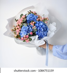 Woman hand hold bouquet of blue hydrangea flowers and pink roses on white background