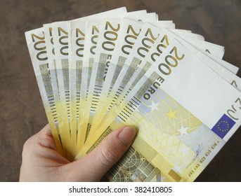 Woman hand hold cash two hundred euro banknotes.