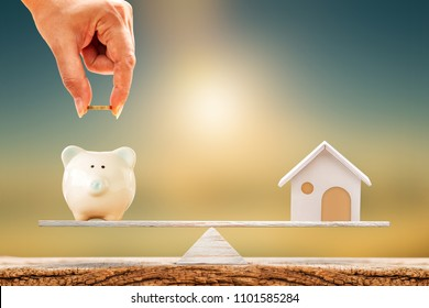 Woman hand hold a coin and piggy bank and home put on the scale with balance put on the wood on sunlight, Saving money for buy a new house or real estate and loan for plan business investment concept.