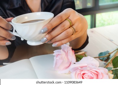 woman hand hold a cup of coffee at workspace