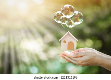Woman hand hold a home model hanging crystal balloon with money bag stay inside with soar in the garden, Saving money for buy a new house or loan for plan business investment of real estate concept.
