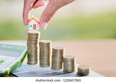 Woman hand hold a  home model put on the stack coin with growing, Savings money for buy house and loan to business investment for real estate concept.