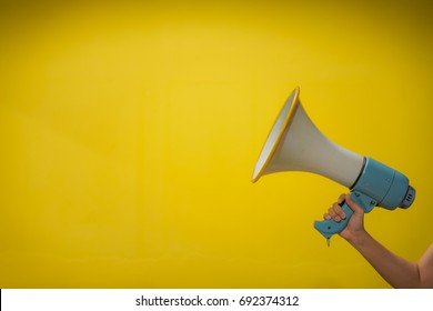 woman hand hold megaphone, yellow background