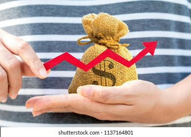 Woman hand hold a money bag and red arrow graph with growing value, Currency and financial business investment to future and fund concept.