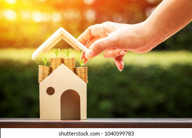 Woman hand hold to open a roof and a coin stack substantial savings money inside the house and plant growing on the top in the public park, Business investment or loan for real estate concept.