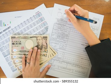 Woman hand hold pen fill in the details on the tax forms paper with yen moneyin business concept