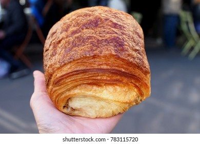 Woman hand hold a piece of Pain au chocolat, a type of viennoiserie sweet roll from Ble Sucre, Paris
