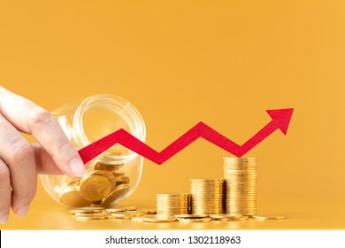 Woman hand hold a red arrow graph with growing value and jar bank and stack gold coins in the office, Saving money for future investment concept.