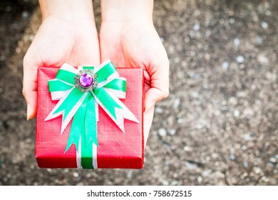 Woman hand hold a red gift box tied with green ribbon for give in the public park, present for Christmas and new year and valentine day or Important occasions concept.