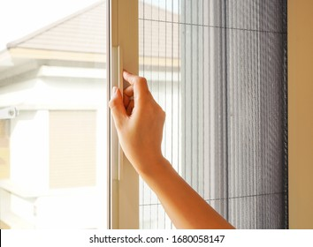 Woman hand hold retractable pleated insect screen holder to open or close the window ,selective focus on the hand