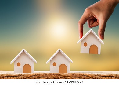 Woman hand hold for select a home model on the wood on sunlight, Loan for real estate or saving money for buy a new house to family in the future concept.
