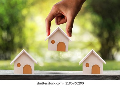 Woman hand hold for select a home model on the wood on sunlight in the public park, Loan for real estate or saving money for buy a new house to family in the future concept.