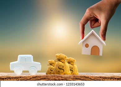Woman hand hold for select a home model and money bag and car on the wood on sunlight, Loan for asset or saving money for buy a new real estate to family in the future concept.