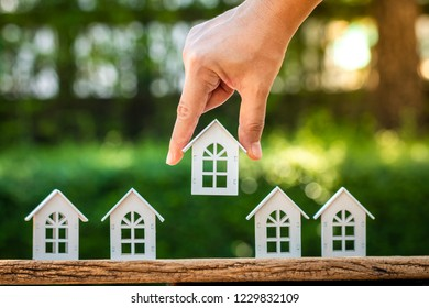 Woman hand hold for select a white wooden home model put on the vintage wood in the public park, Loan for real estate or saving money for buy a new house to family in the future concept.