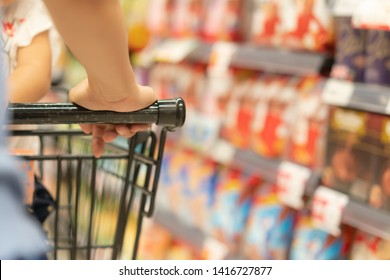 Woman hand hold shopping cart in supermarket