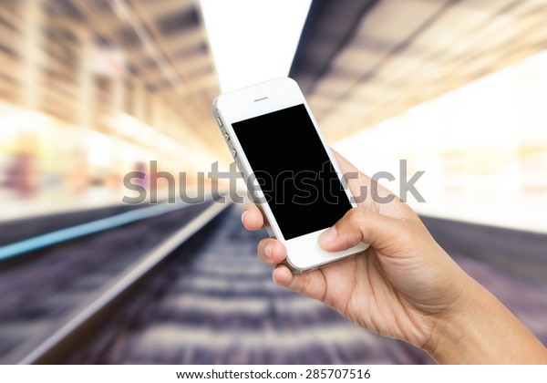 woman hand hold smart phone, tablet,cellphone on blurred of railway station background