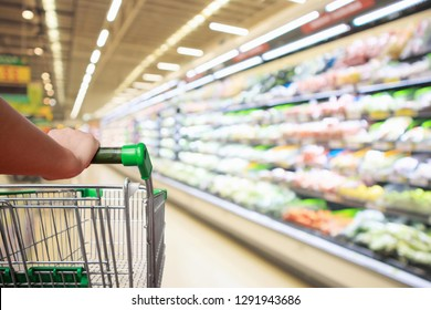 woman hand hold supermarket shopping cart with abstract blur organic fresh fruits and vegetable on shelves in grocery store