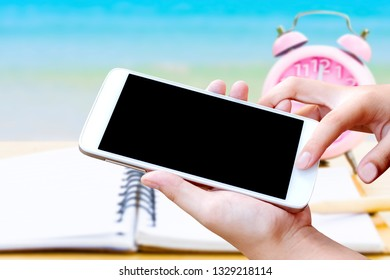 woman hand hold and touch screen smart phone or cellphone  with pink retro clock and note book on wooden table  over blurred  blue sea  on the beach. image for summer shopping online concept