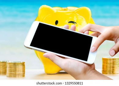 woman hand hold and touch screen of mobile phone or cellphone with yellow piggy bank and stack coins over blurred blue sea ,image for holiday money investment concept.