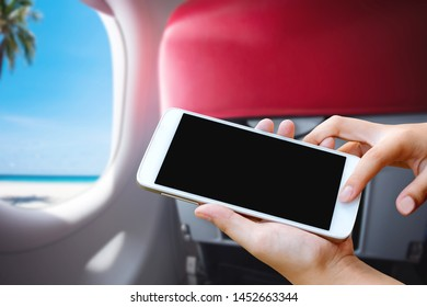 woman hand hold and touch screen smart phone or cellphone in airplane with tropical blue sea view. Image for travel vacation concept.