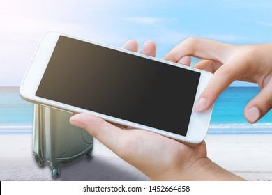 woman hand hold and touch screen smart phone or cellphone with travel suitcase over tropical blue sea background. Image for travel vacation concept.