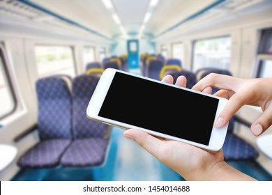 woman hand hold and touch screen smart phone or cell phone over Empty interior of the train for long and short distance in Europe train carriage with blue seats. background.