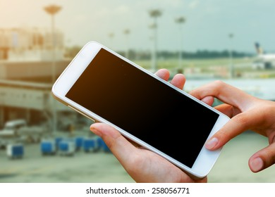 woman hand hold and touch screen smart phone,tablet,cellphone in cargo of  airport terminal