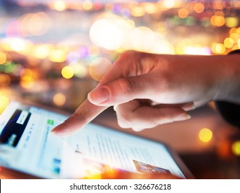 Woman hand hold and touch screen tablet on abstract blurred bokeh of city night light background. Focus in the foreground.