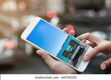 woman hand hold and touch screen with tropical spring summer beach solution concept on smartphone or cellphone over blurred urban city traffic background,image for booking travel holiday concept.