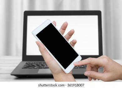 woman hand hold and using mobile,cell phone,smart phone,tablet over blurred image of notebook,black and white tone background