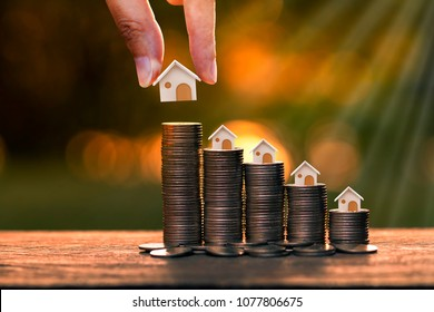 Woman hand hold a wooden home model put on the stack coin with growing in the public park, Savings money for buy house and loan to business investment for real estate concept.