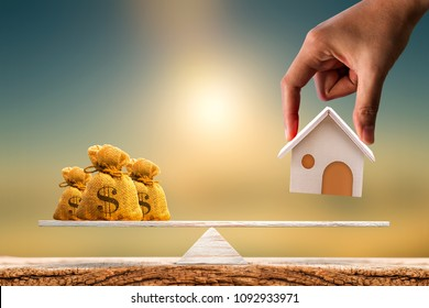 Woman hand hold a wooden home model and money bag put on the scales with balance put on the wood on sunlight, Saving for buy a new house or real estate and loan for plan business investment concept.