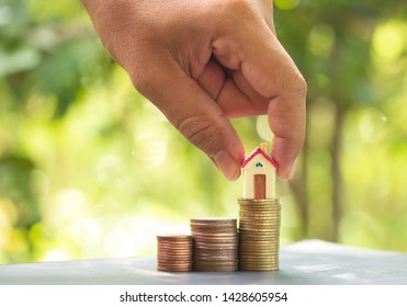 Woman hand hold a wooden home model put on the stack coin with g