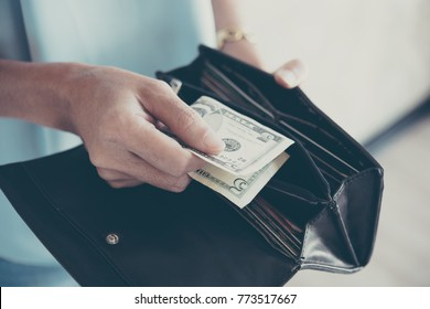 woman hand holding American currency of five dollar bills, spending and shopping for human desire, world of business and using money.