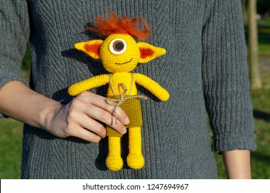a woman hand, holding an amigurumi crochet doll. knitted cyclops monster on a woman hand.
